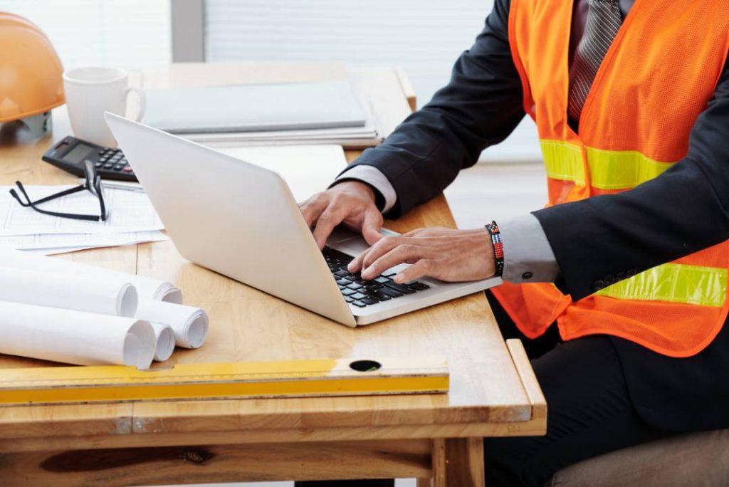 Un uomo in completo con gilet arancio che lavora al PC