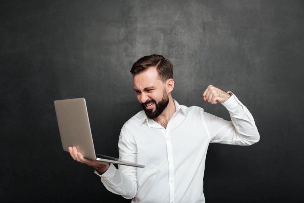 Un uomo arrabbiato che vorrebbe spaccare il PC