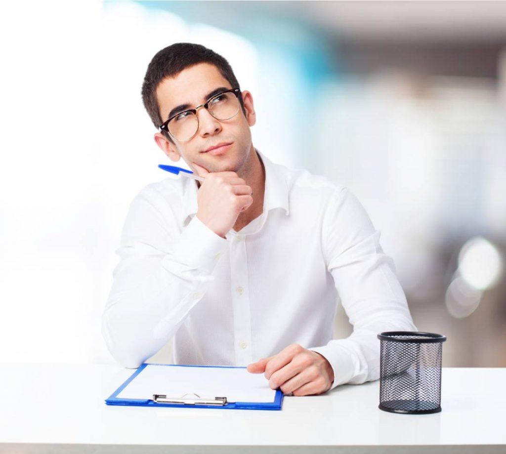 Un uomo seduto ai un tavolo mentre pensa