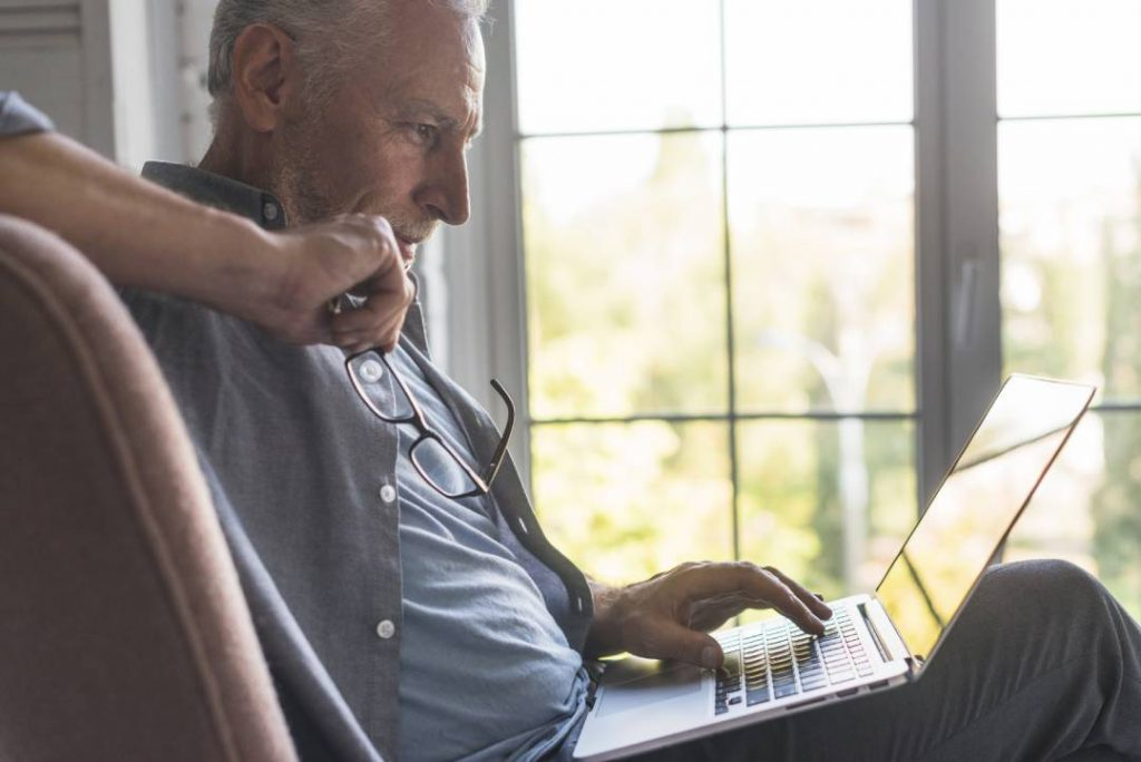 Un uomo al PC che morde gli occhiali