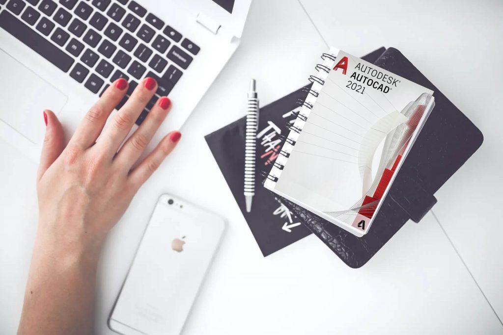 Una ragazza al PC con un book Autodesk AutoCAD