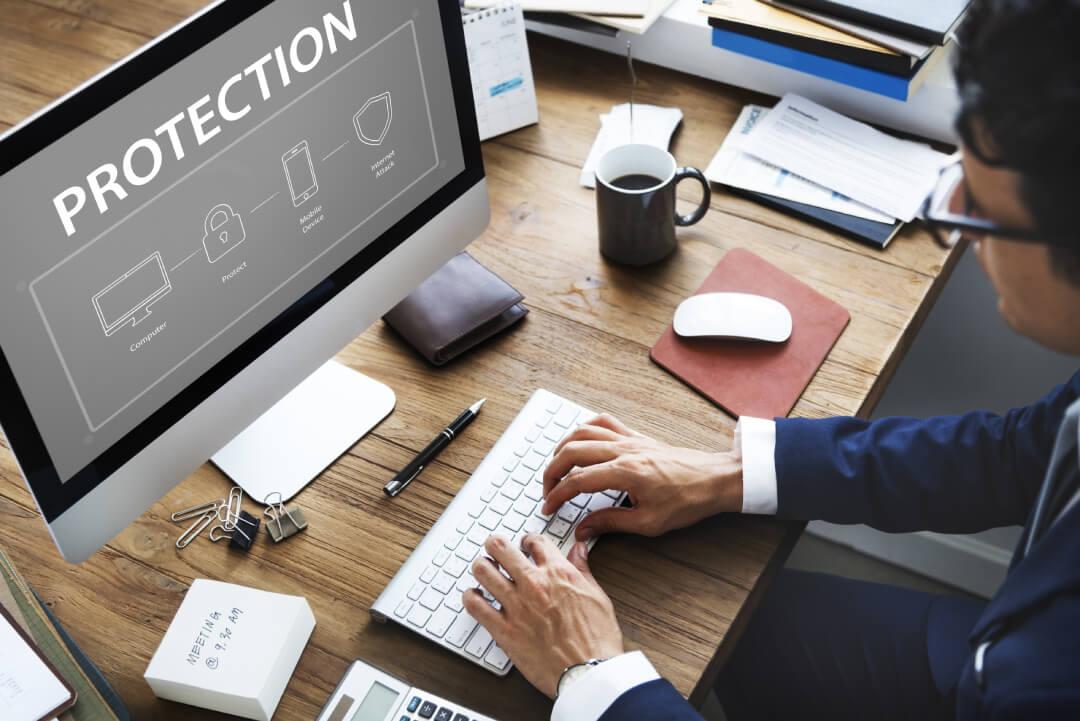 Una persona al PC mentre lavora alla sicurezza informatica